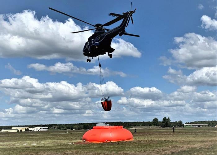 Waldbrand Behälter wird vom Hubschrauber aufgefüllt